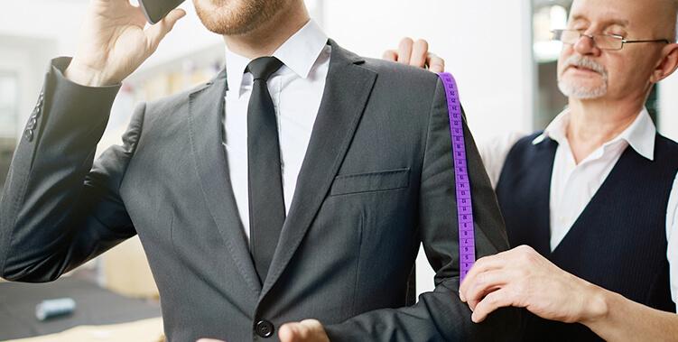 Tailor measuring a suit